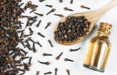 Close up glass bottle of clove oil and cloves in wooden spoon on white rustic table. Essential oil of clove rustic style background spice concept