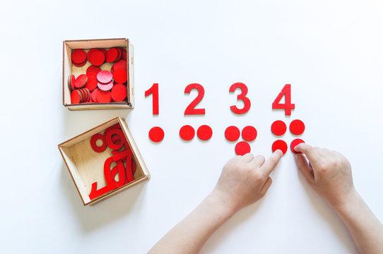 Montessori material. Children's hands. The study of mathematics