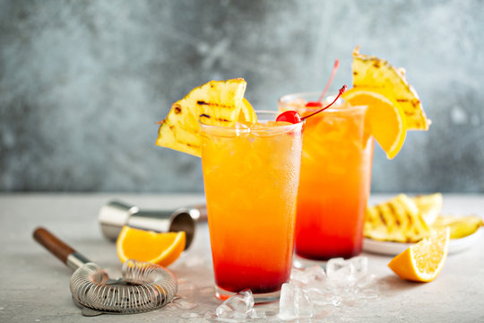 Tequila sunrise cocktail with grilled pineapple and orange