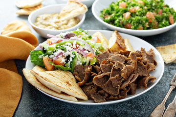 Mediterranean food on the table, gyro platter, pita and dips and tabbouleh