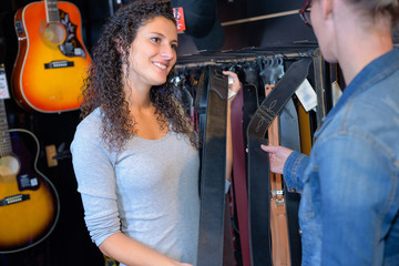 Tuinposter Muziekwinkel shop assistant showing guitar to customer