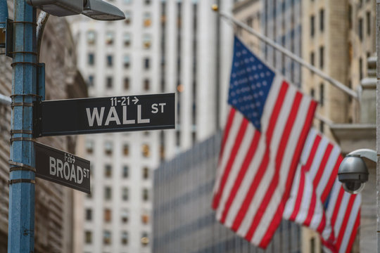 """Wall Street """"WALL ST"""" sign and broadway street over American national flags in front of NYSE stock market exchange building background. The New York Stock Exchange locate in economy district"""