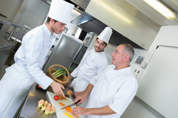 professional chef and his trainees cooking fresh vegetable salad