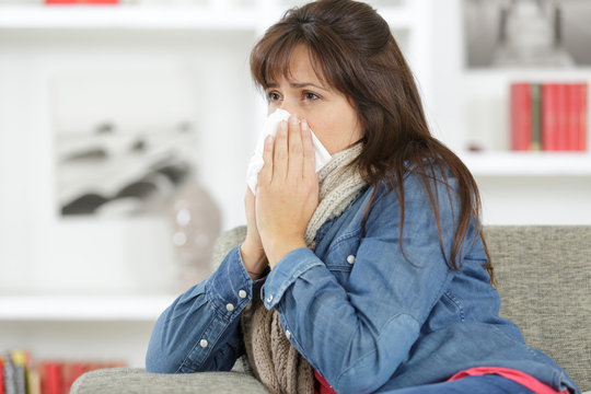 sick woman sneezing on the sofa
