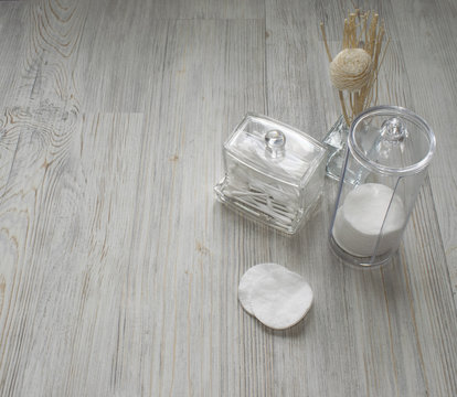 Cosmetic flatlay on grey wooden table. Beauty set of plastic containers with Q-tips and disks. Space for text.