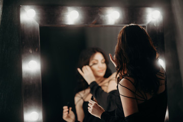 beautiful elegant brunette in a black silk dressing gown is standing in front of a tall make-up mirror and dressing herself up, paints eyelashes with mascara in a gray luxurious bathroom