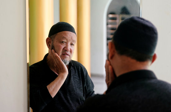 A muslim man looks in the mirror during the holy month of Ramadan at a mosque, in Shanghai