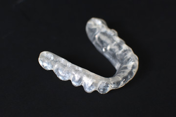 Customized transparent teeth bite guard clear aligners for lower jaw on dark black background