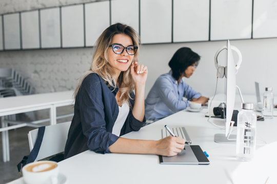 Beautiful female office worker carrying out administrative work for company. Indoor portrait of cute blonde student doing homework with asian universuty friend.