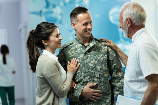 Happy military officer and his wife talking to a doctor in a hallway at clinic.