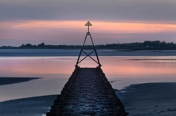 A Cardinal sailing marker at sunset on a calm tide on The Loughor Estuary, Llanelli, South Wales, UK