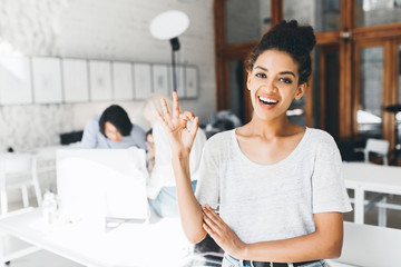 Glad african woman in white t-shirt posing with okay sign in front of busy colleague. Indoor portrait of excited black girl having fun in office during break. Wall mural