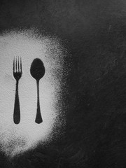 Spoon and fork silhouette made with flour on dark texture background