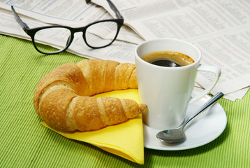 Small quick breakfast with croissant and newspaper, copy space