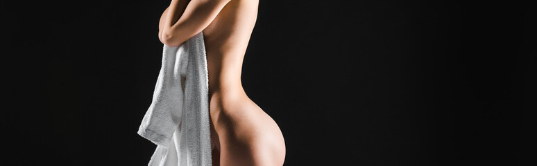 panoramic shot of sexy half-naked young woman holding white bathrobe and posing isolated on black