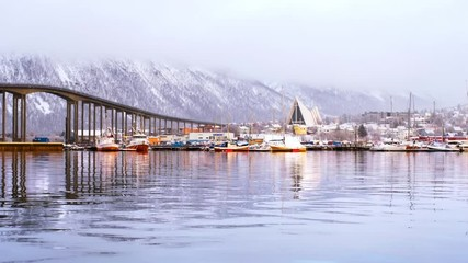Wall Mural - Tromso, Norway. Time-lapse during the cloudy day of famous north town Tromso, Norway. View of the fjord with houses, mountain and beautiful bridge, zoom in