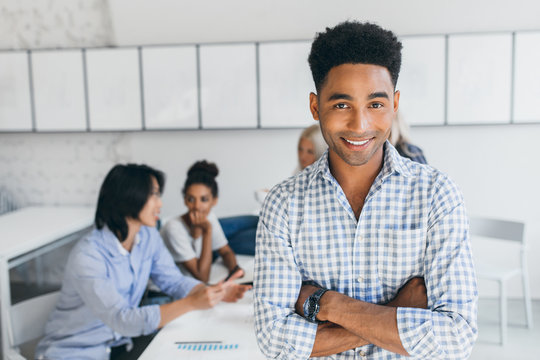 Glad young man with african hairstyle posing with arms crossed in his office with other employees on background. Male manager in blue shirt smiling during conference at workplace.