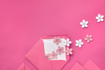 Springtime flat lay on pink paper with decorative wihte and peach colored flowers flying from open envelope