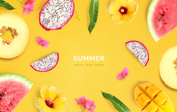 Creative layout made of melon, watermelon, dragon fruit, mango and flowers on yellow background.  Tropical flat lay. Summer fruits concept.