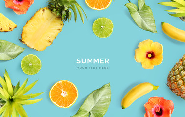 Creative layout made of pineapple, banana, orange fruit, lime and flowers on blue background.  Tropical flat lay. Summer fruits concept.