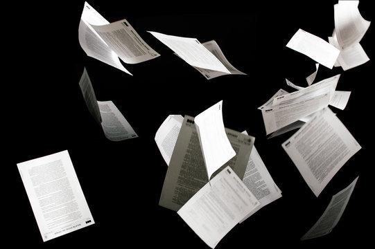 Many flying business documents isolated on black background