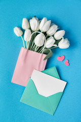 Springtime flat lay, white tulips in paper bag on blue mint background with envelope, blank card and decorative hearts