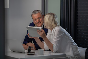 A middle aged couple sitting at the table. A man in glasses is smiling looking at the tablet that his wife is holding in hands. There is an opened laptop on the table in front of them