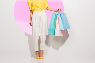 partial view of stylish girl holding colorful shopping bags on white with pink circle