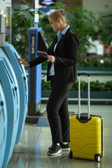 A young fair haired woman is standing near the self check terminal in an airport. She is holding her opened passport in one hand and entering data with another. There is a bright yellow suitcase near