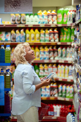 A smiling middle aged woman in a light blue shirt is standing in a household section of a supermarket. She is holding a tablet and a red shopping basket in her hands. A woman is looking at the shelves