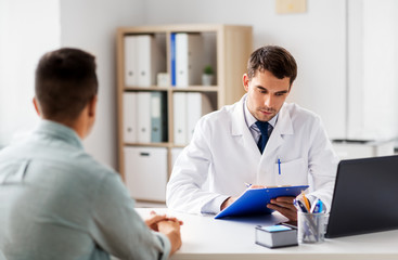medicine, healthcare and people concept - doctor with clipboard and male patient at medical office in hospital
