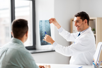 medicine, healthcare and people concept - smiling doctor showing x-ray to patient at medical office in hospital