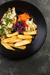 Grilled chicken breast with fries and salad, restaurant serving plate