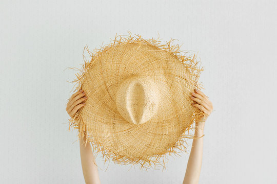 Female hands hold  Summer straw hat. Vacation concept