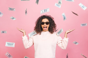 Concept photo of a cheerful afro american woman standing under rain with money isolated against pink background.