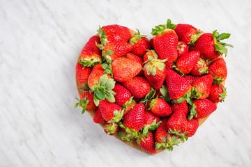 Heart shape strawberries on white marble, love for fresh fruits