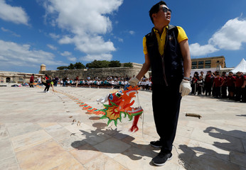 Kite makers prepare to fly a long dragon kite as school children look on during the Chinese Kite Festival in Valletta