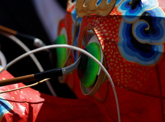The eyes of a dragon kite are touched up before flying during the Chinese Kite Festival in Valletta