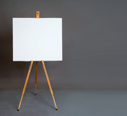 White empty artistic canvas on an easel for drawing images by an artist on a gray background in the studio