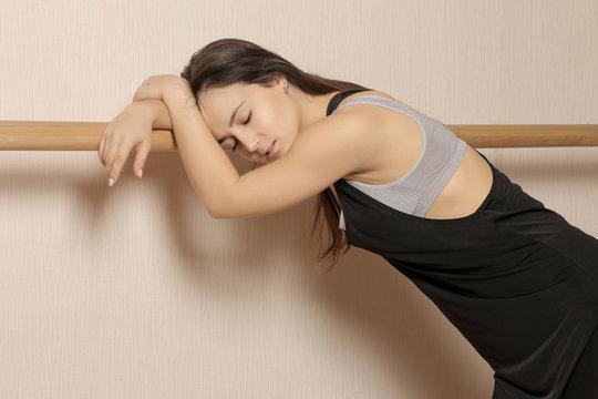 Beautiful girl dancer. tired girl dancer. girl ballerina or dancer is standing and resting near the ballet barre in a dance studio.