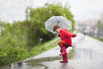 Obraz little child boy with an umbrella playing out in the rain in the summer outdoors - fototapety do salonu
