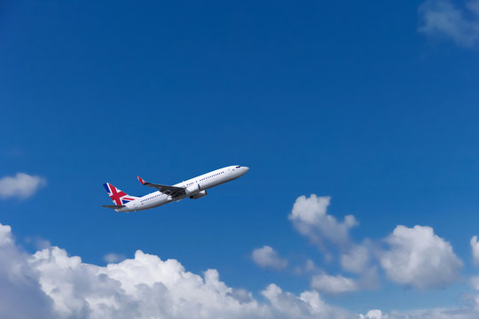 Custom commercial passenger aircraft with british flag on the tail. Blue cloudy sky in the background