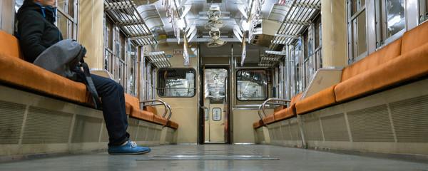 Japanese man in empty train at night 夜の電車内部 座席に座る男性