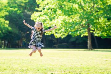 芝生でジャンプする可愛い女の子