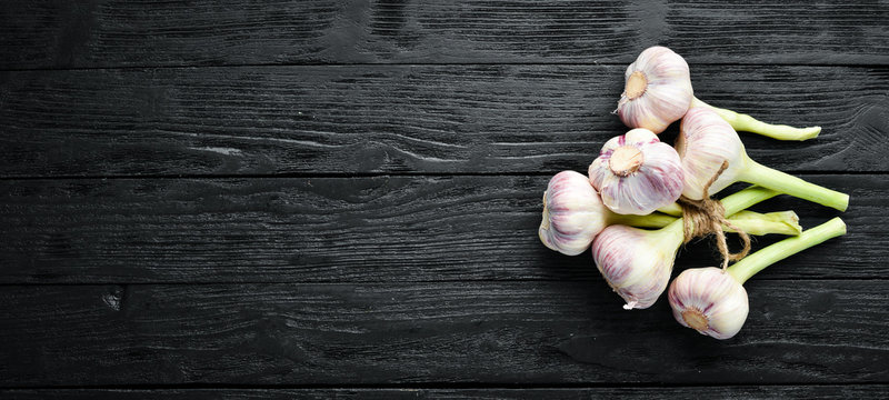 Fresh garlic on a wooden background. Top view. Free space for your text.