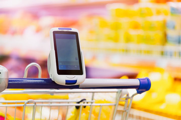 Close up of bar code scanner on shopping cart in store. Concept of modern gadgets
