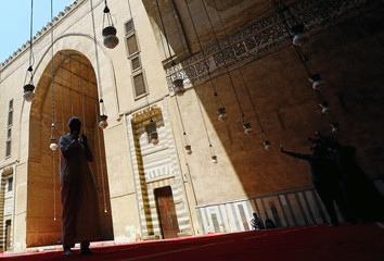 People take a selfie picture while an Egyptian Muslim prays after Friday prayers inside Al Sultan Hassan mosque during the Muslim holy fasting month of Ramadan in the old Islamic area of Cairo