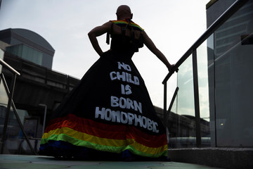 An LGBT activist wearing a dress with a message poses for pictures as she attends an International Day Against Homophobia, Transphobia and Biphobia at Bangkok's Art Center