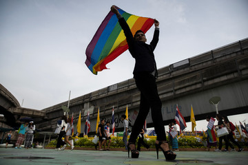An LGBT activist holding a rainbow flag poses for pictures as he attends an International Day Against Homophobia, Transphobia and Biphobia at Bangkok's Art Center