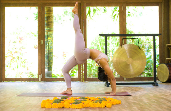 young attractive and healthy Asian Indonesian acrobat woman practicing acro yoga exercise in balance pose at traditional studio training concentrated in harmony